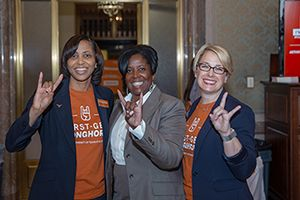 Faculty throwing the 'Hook 'em' sign.