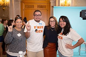 Students with Senior Vice Provost for Enrollment Management Rachelle Hernandez throwing 'Hook 'em' sign.