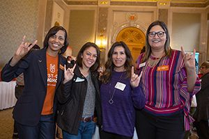 Faculty and staff throwing the 'Hook 'em' sign.